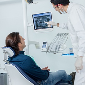 Dentist and male patient looking and dental x-rays